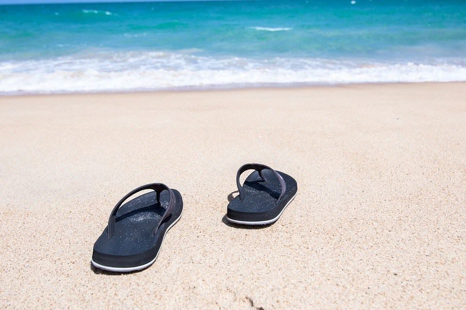 Healthy vacations: photo of flip-flops on a sandy beach