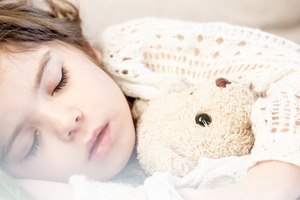 Little girl sleeping peacefully with teddy bear