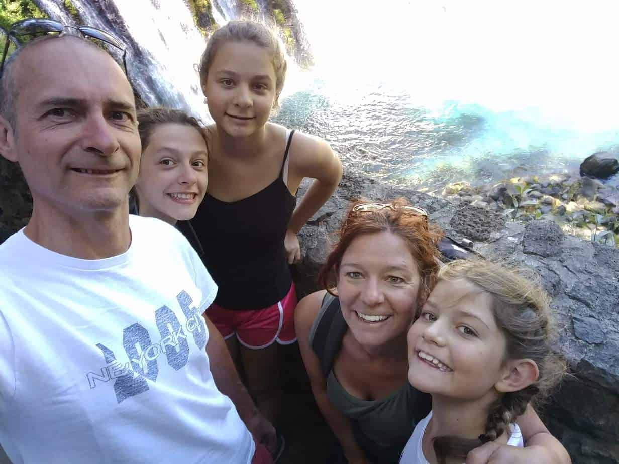 family on a hike with waterfall in the background