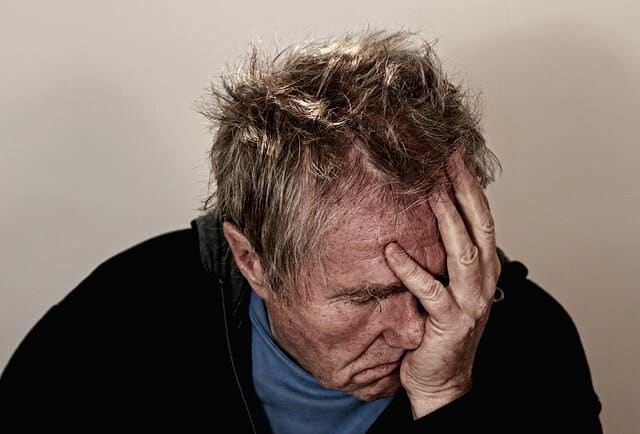 Man suffering from headache because of alcohol consumption