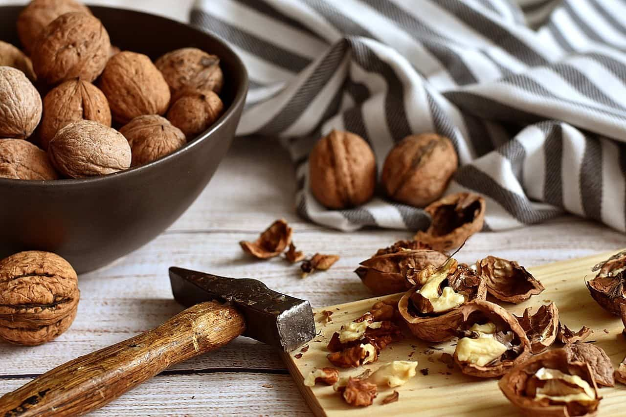 Walnuts in their shell in  a bowl and on a table, to help reverse prediabetes