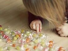 Child counting candy on the floor, to illustrate calorie counting