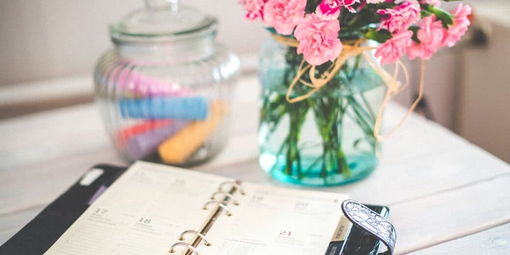 Planner on a table next to a vase with flowers