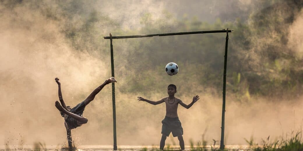 children scoring a goal playing soccer