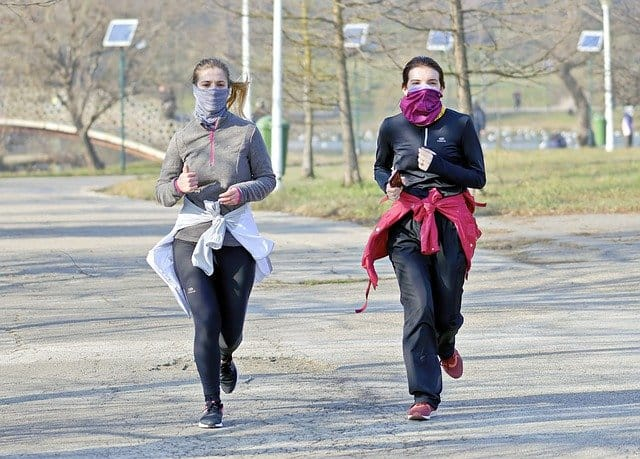 two young women jogging while wearing masks