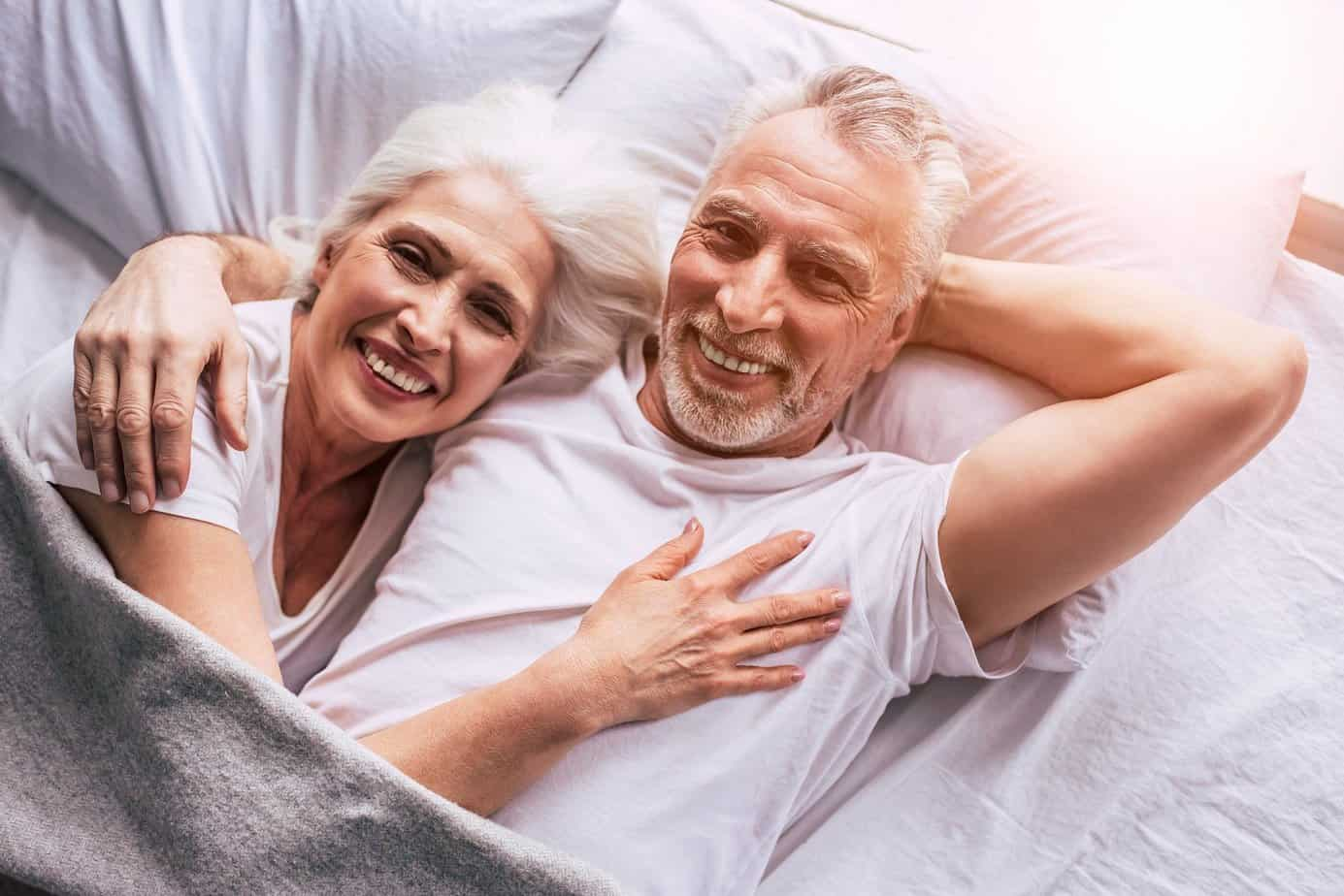 healthy couple of senior smiling in bed